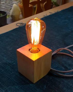 Kleine Lampe mit Lampenfuß aus Kantholz, beleuchtet